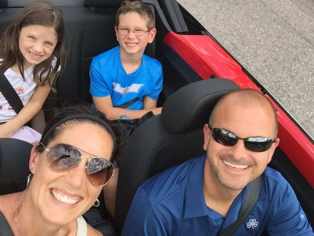 A red convertable with the top down and  a family of four smiling.
