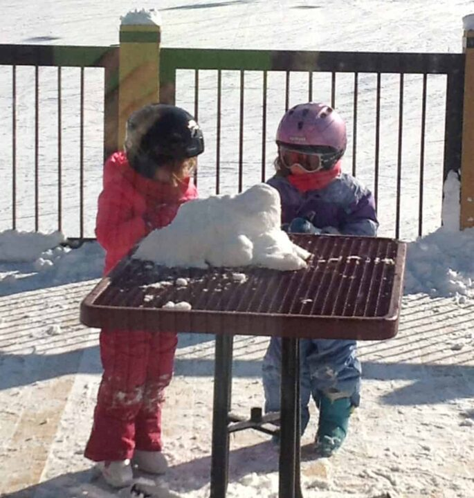 little girls in ski gear playing with snow
