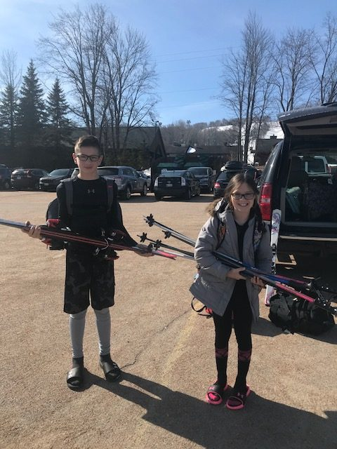 kids holding skis in a parking lot