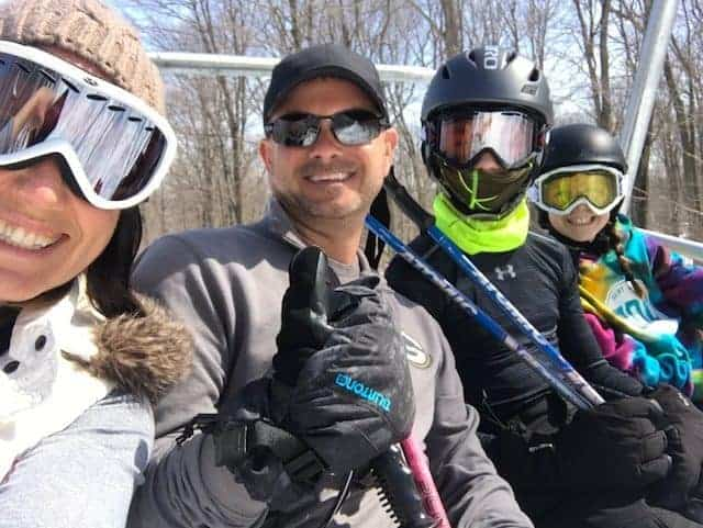 A group of people posing for the camera on a ski lift