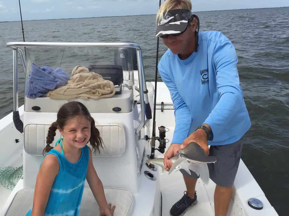 A chartered fishing boat with the guid holding a small hammer head shark and a 5 year old girl smiling close by.