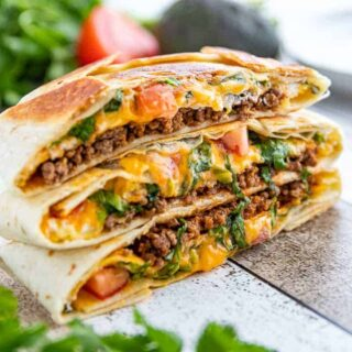 three stacked Crunchwrap supremes with beef and cheese oozing out.