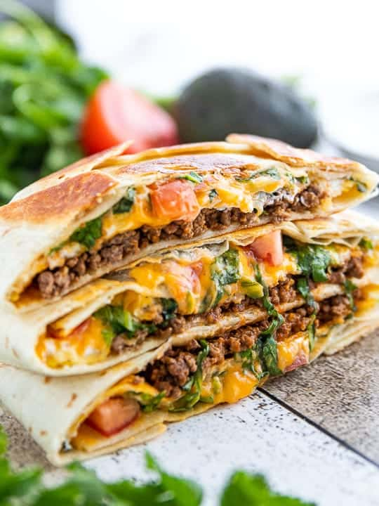 crunchwrap supreme recipe shown cut in half with juicy meat and cheese showing