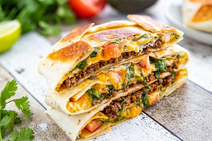 Crunchwrap Recipe shown cut in half with ground beef, tomatoes, lettuce and cheese showing stacked up three high.