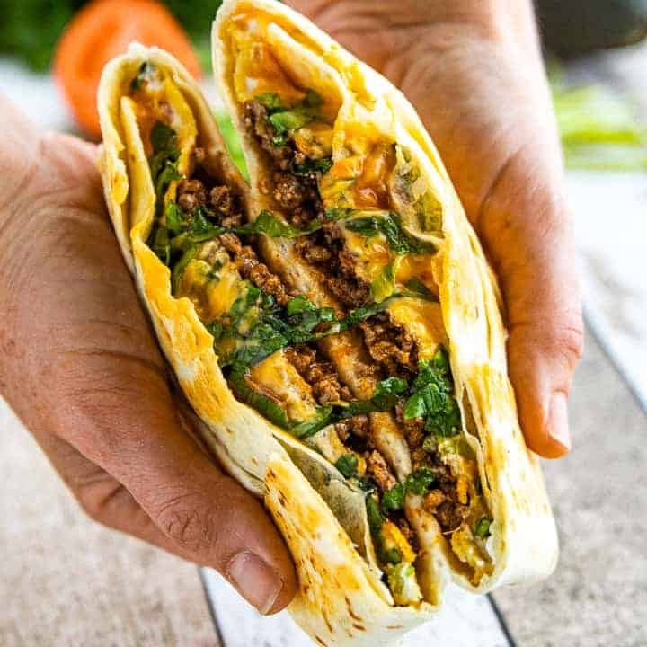 Crunchwrap supreme recipe shown cut in half with two hands folding it open where its sliced.