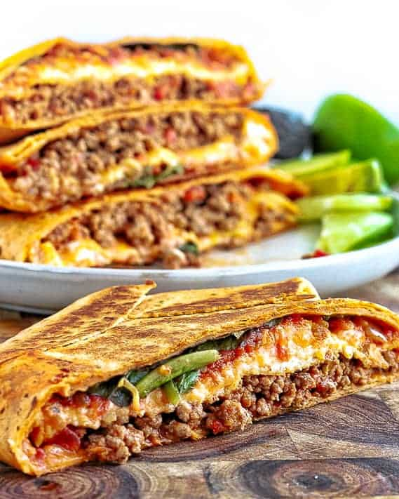 Crunch Wrap Supreme Recipe shown cut in half with ground beef, tomatoes, lettuce and cheese showing with a stack of crunch wraps in the background.