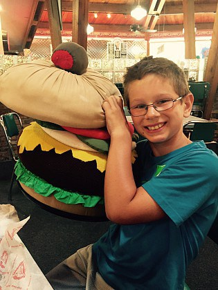 A 7 year old boy holding the giant stuffed hamburger at Chee burger Chee burger.
