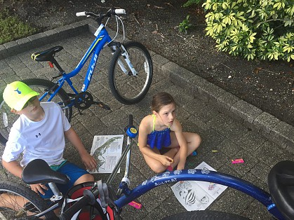 2 small children sitting next to the bikes filling out a paper.