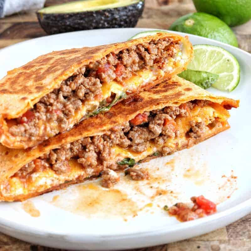 crunch wrap supreme shown cut in half on a white plate with juicy meat and cheese showing