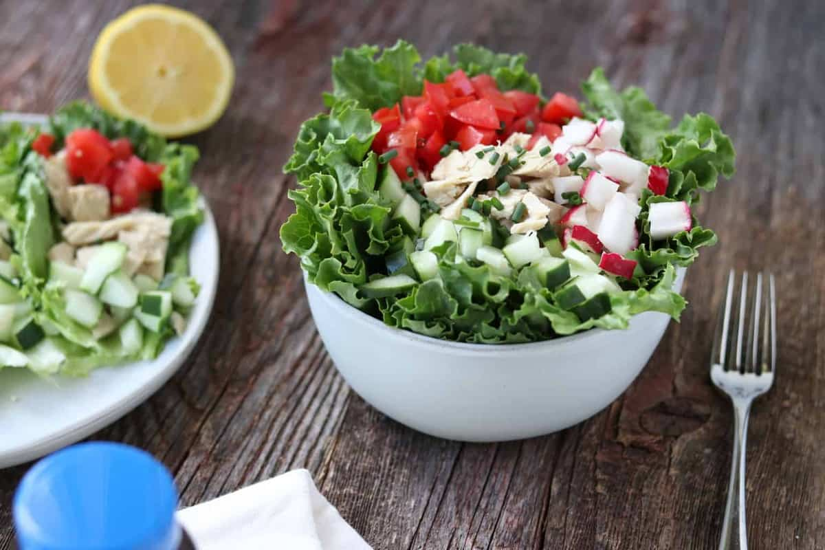 A lettuce salad in a white bowl with a fork and lemon next to it. The salad has tomatoes, radishes, cucumbers and tuna on top. There is another salad to the left on a plate with only half the plate showing.