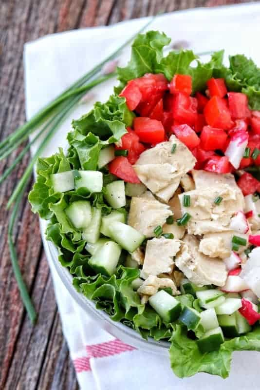 Looking down at a lettuce salad with chopped cucumber, tomato, radish, and tuna in a white bowl on a white dish cloth with chives on a wood surface