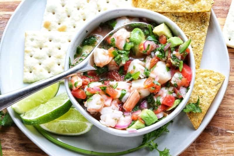 Mexican Shrimp Ceviche Recipe in a white bowl with silver spoon on a white plate surrounded by crackers, tortilla chips, sliced limes, and fresh cilantro