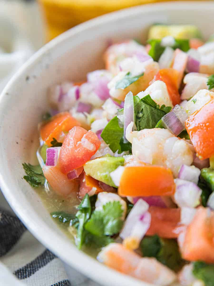 Shrimp Ceviche in a white bowl shown up close with sliced shrimp, avocado, fresh tomatoes, cilantro, and hot sauce.