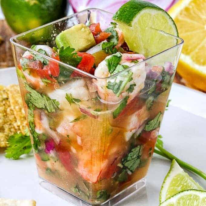 Mexican Shrimp Ceviche recipe served in a small clear individual serving up, garnished with lime on a white plate next to tortilla chips, lime, and cilantro.