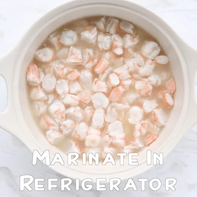 Cooked and chopped shrimp marinating in lemon and lime juice in a white flat bottomed bowl with handles with the words Marinate in Refrigerator.