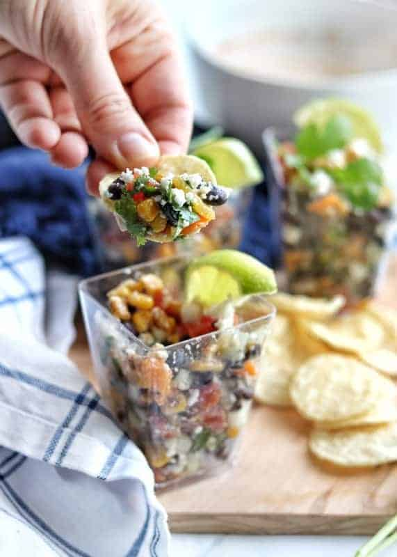 A small individual clear serving cup with Mexican street corn salad on a wooden board with tortilla chips, a white and blue checked kitchen towel with another cup in the background. There is a hand with a chip scooping the Mexican corn salad on to it in focus.