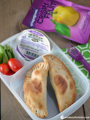 A 3 compartment clear lunch container with 2 empanadas, wholly guacamole and veggies with a purple pouch of crispy fruit on the side.