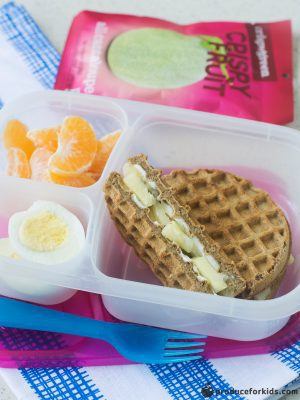 A 3 compartment lunch container with a waffle sandwich, hardboiled egg, and clementine with a package of dried fruit in the background.