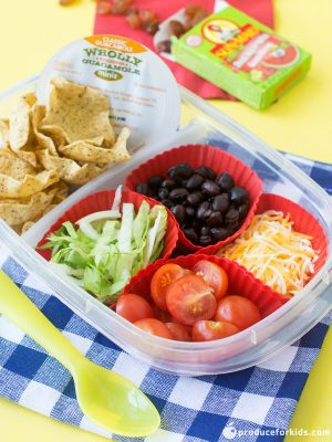 A clear 2 compartment lunchbox container with nacho makings- tortilla chips, shredded lettuce, tomato, cheese, and beans on top of a blue checkered napkin, yellow spoon, and raising in the background.