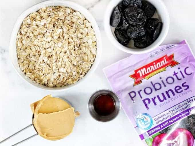 Ingridients displayed on white surface, dry oats, peanut butter in a metal measuring cut, Mariani probiotic prunes bag and a white bowl with prunes in it and a small metal cup of vanilla
