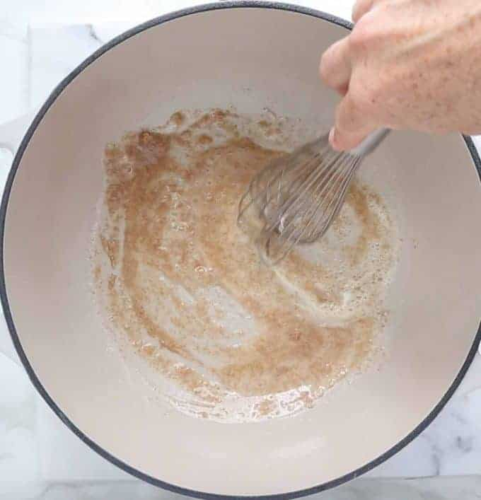 how to make Mac and cheese: top down view of white sauce pan with butter and flour being whisked by hand