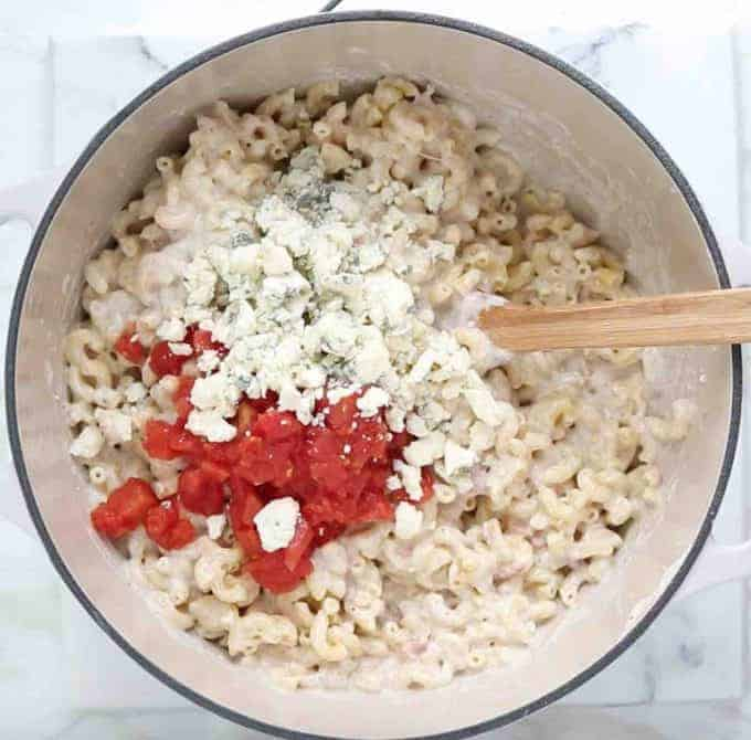 how to make Mac and cheese: top down view of white sauce pan with elbow Mac mixed with cheese sauce and diced tomatoes and blue cheese crumbles on top with a wooden spoon in the bowl.