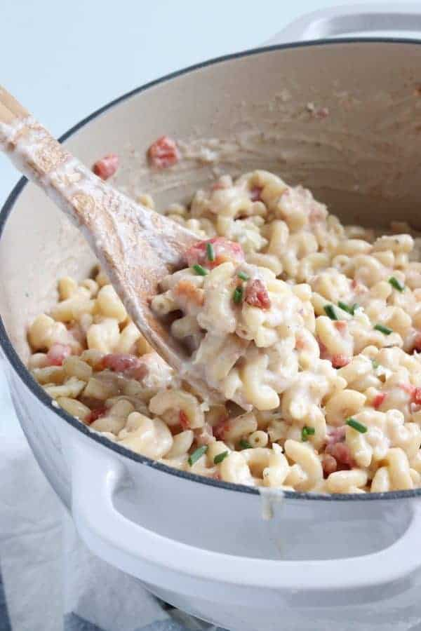 A white sauce pan filled with finished creamy Mac and cheese. A wooden spoon is in the bowl showing the Mac and cheese with tomatoes, bacon, and garnished with chives.