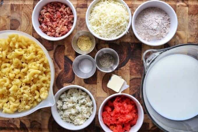 Ingredients in bowls for Mac and cheese including elbow macaroni, blue cheese crumbles, bacon bits, white cheese, flour, milk, ground mustard, salt, pepper, and diced tomatoes all on a wooden cutting board shown top down.