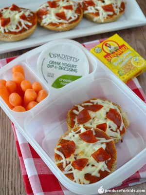 a 3 compartment clear lunchbox container filled with 2 bagel pizzas, carrots, and greek yogurt dip on top of a red checked napkin with 3 more pizzas in the background and a box of raisins.