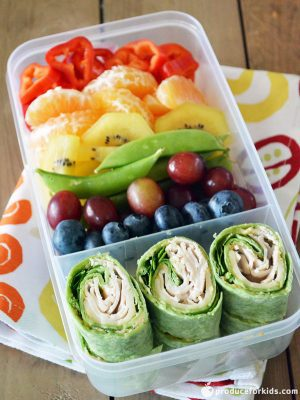 2 compartment clear lunch container with rainbow fruit and vegetables in one compartment and turkey roll ups in a spinach wrap in the other.