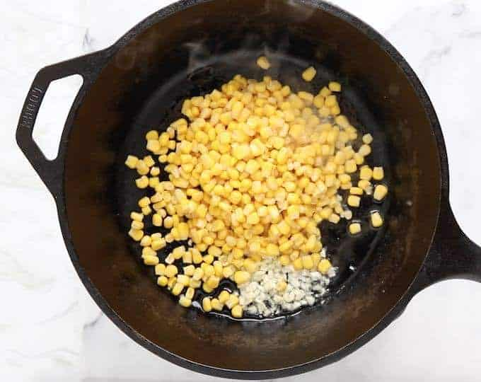 Canned corn, minced garlic and olive oil in a cast iron pan on a white surface