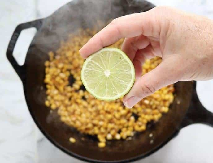 Half a fresh lime held in on hand over a pan of charred corn in a cast iron pan on a white marble surface.