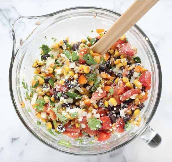 A clear glass bowl with a handle and spout containing mixed Mexican corn salad with corn, tomatoes, onion, peppers, black beans, cilantro, and cotija cheese with a wooden spoon on a white marble table.