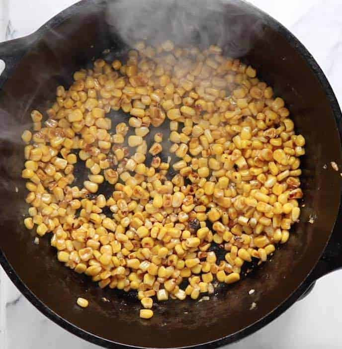Charred corn in a cast iron pan on a white marble surface