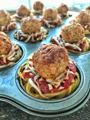 A muffin tin of spaghetti and meatball cups are shown at an angle with a close up of a meatball on top of sauce and spaghetti in a muffin cup.