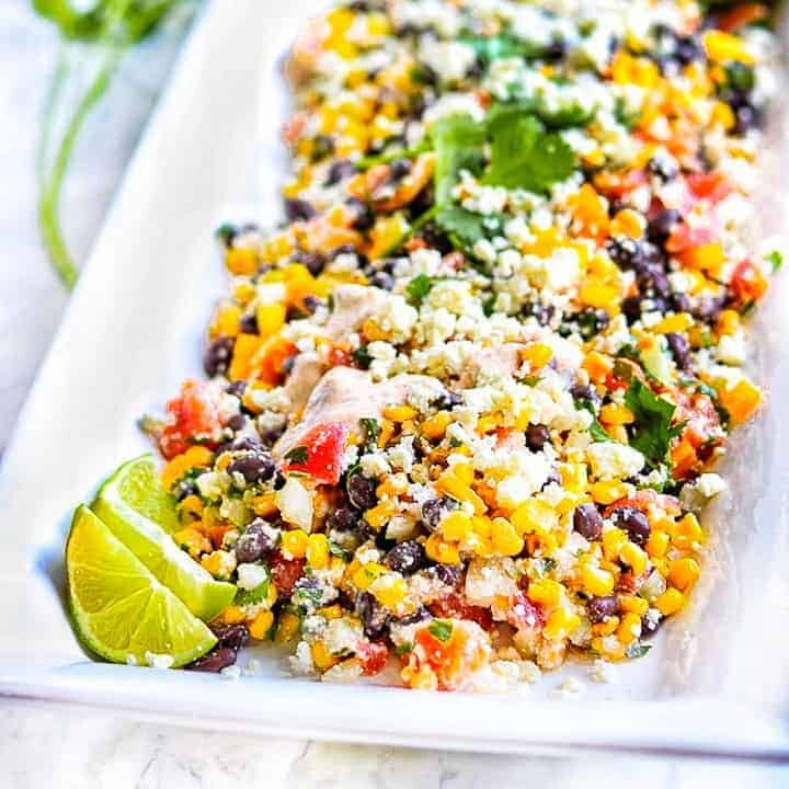 canned Mexican corn salad shown on a white tray.