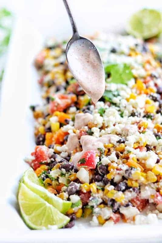 Mexican street corn salad with corn, black beans, cojita cheese, lime, and cilantro on a white plate with a silver spoon drizzling a yogurt based dressing on top.