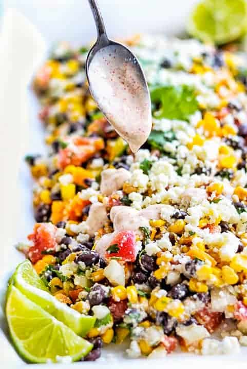 canned Mexican corn salad with corn, tomato, black beans, cotija cheese, cilantro and limes on a white platter with a spoon drizzling a yogurt based dressing on top.