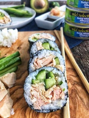 Tuna sushi rolls lined up on a wooden board next to chop sticks, tuna chunks, some rice, and with canned tuna in the background along with a white plate with more sushi, cucumber slices, and an avocado.