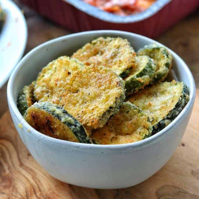 Zucchini crisps are shown stacked in a white bowl on a wooded surface.