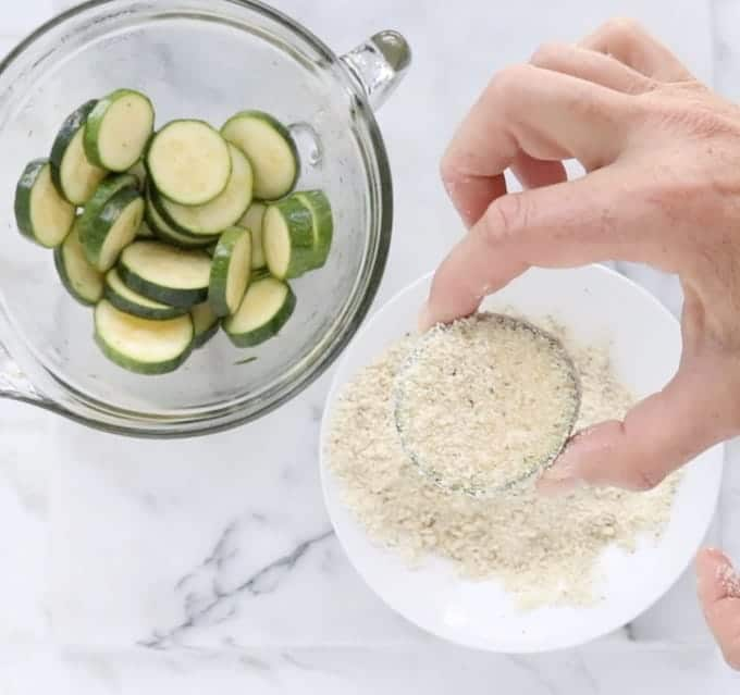raw zucchini round is coated in panko crumbs next to a bowl of zucchini slices and panko crumbs on a white marble surface.
