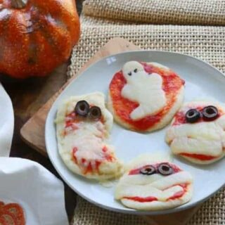 halloween pizza in the shapes of ghosts and mummies on a white plate.