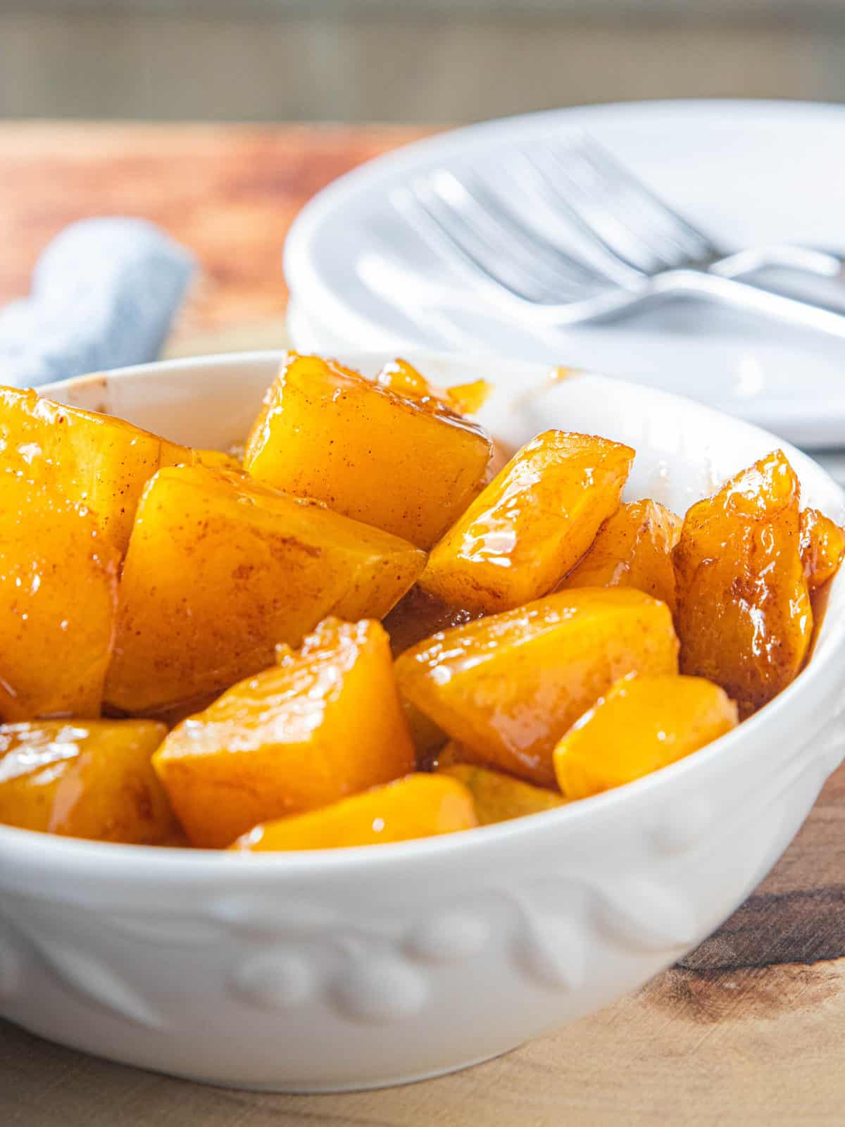 Roasted diced butternut squash in a white bowl glistening with the caramelized sugar.