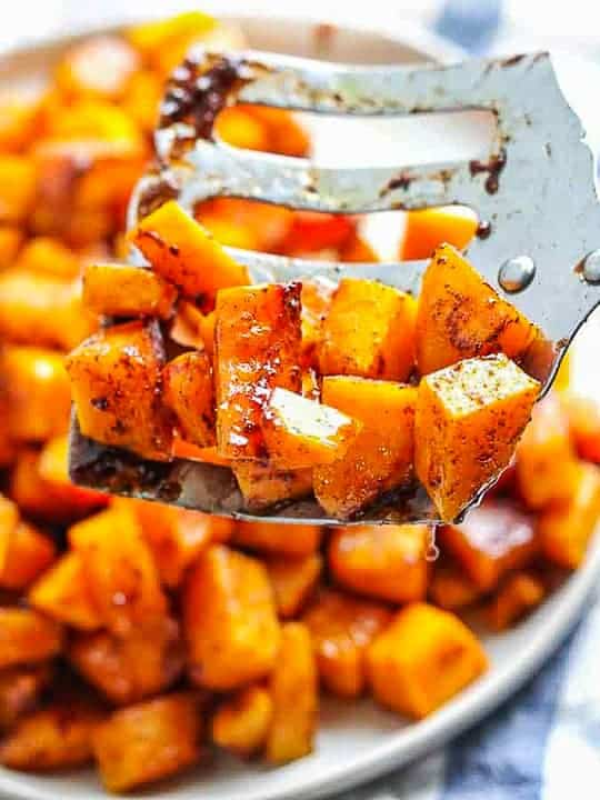 roasted butternut squash brown sugar shown baked in cubes on a white plate with a metal spatula.