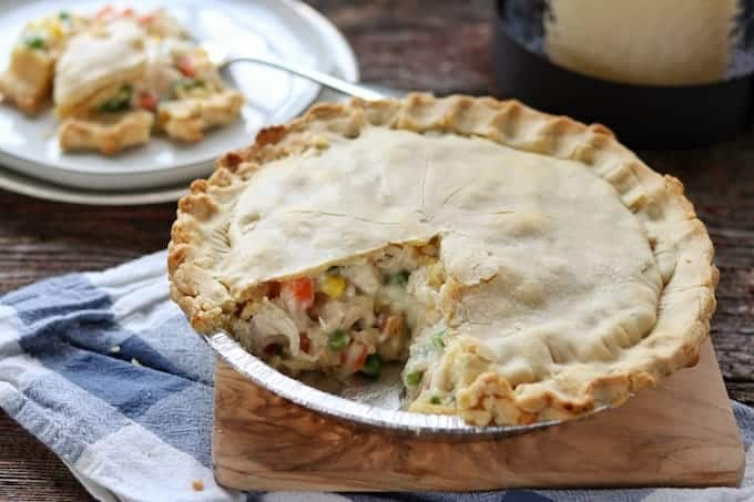 Easy chicken pot pie recipe with pie crust shown baked with one slice removed and shown on a white plate in the background.