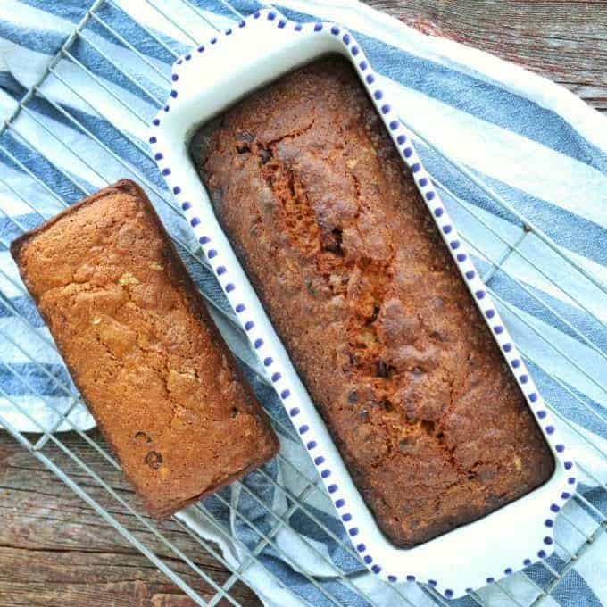 Easy chocolate chip banana bread shown baked in 2 loafs on a wire rack with a kitchen towel underneath.