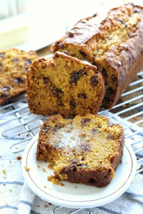 Chocolate Chip Pumpkin Bread Recipe shown sliced on a white plate with melted butter. In the background is the rest of the loaf shown packed with chocolate chips.