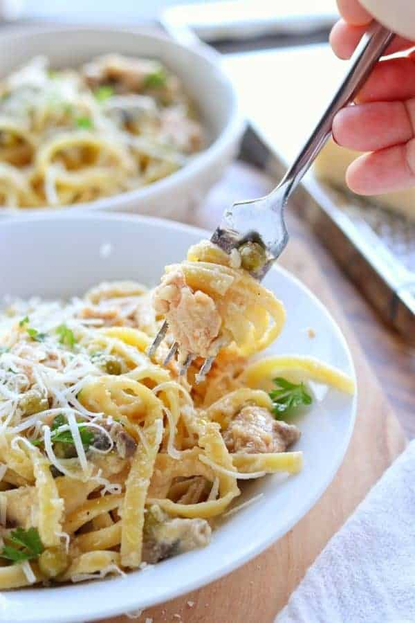 easy Salmon pasta shown in a white bowl with canned salmon, canned peas, canned mushrooms with fresh cheese on top with a fork full of pasta held in a hand.