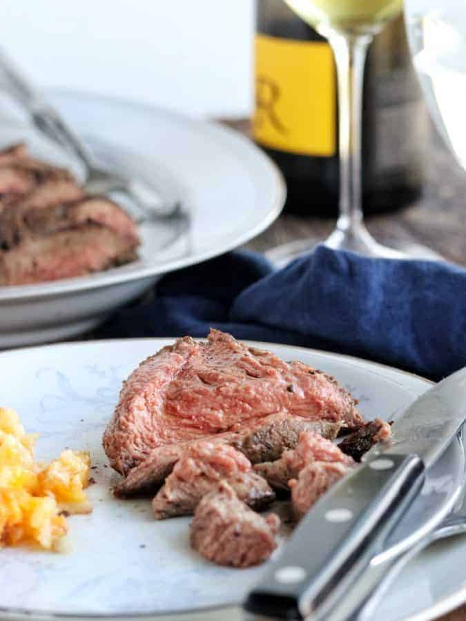 Whole Beef Tenderloin Steak Recipe In The Oven showing the finished steak on a white plate with a steak knife with a glass of wine and platter of steak in the background.