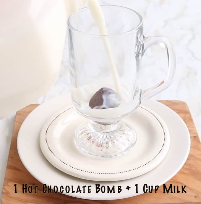 Homemade Hot Chocolate mix Recipe being made showing milk being poured on top of a hot chocolate bomb in a clear glass mug.